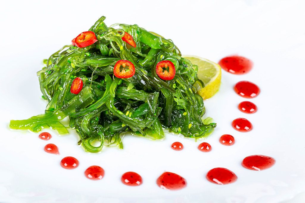 Japanese seaweed chuka salad. Served with lemon, sauce and chunks of hot pepper