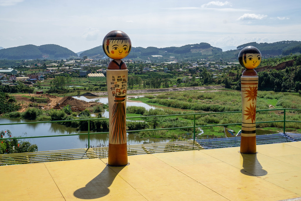 Japanese Themed Characters on a Sun Terrace with View of Mountains and a Village in the Background in Dalat, Vietnam