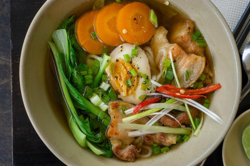 Japanische Ramen Nudelsuppe mit Bok Choy Gemüse, gekochtem Ei und Schweinefleisch Nahaufnahme