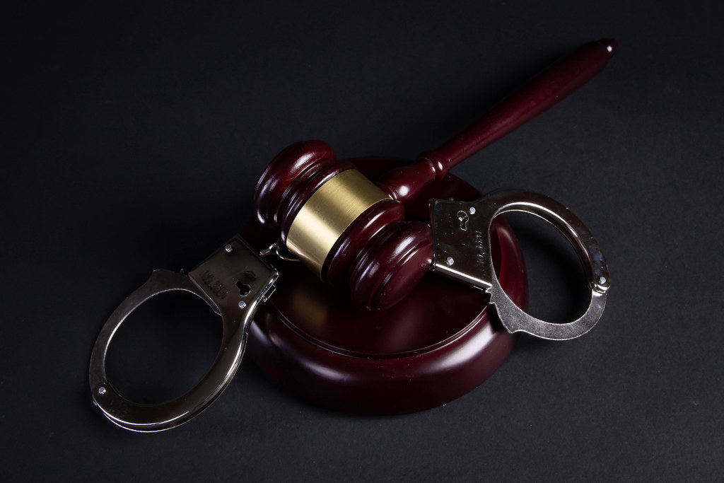 Judge's gavel and handcuffs on black background