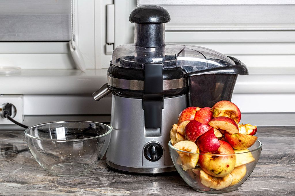 Juice extractor and sliced freshly squeezed apple on kitchen table