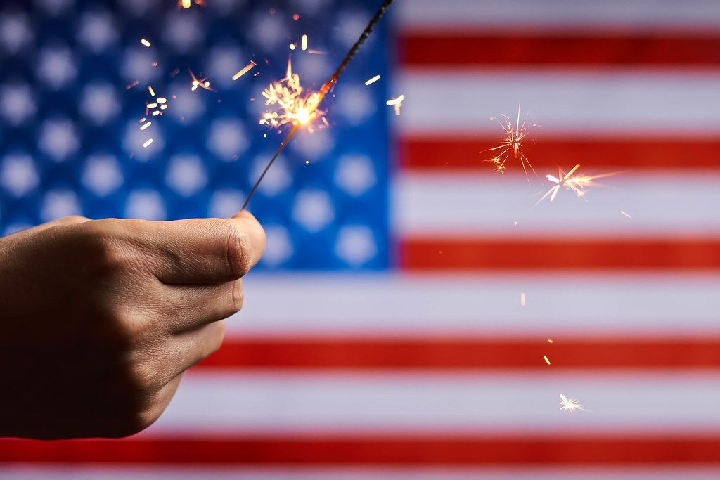 June 14 - US Flag Day. Celebration of American national holiday with sparklers against the American flag