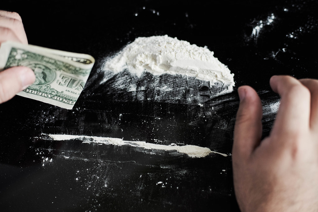 Junkie man making lines of cocaine white powder for snorting