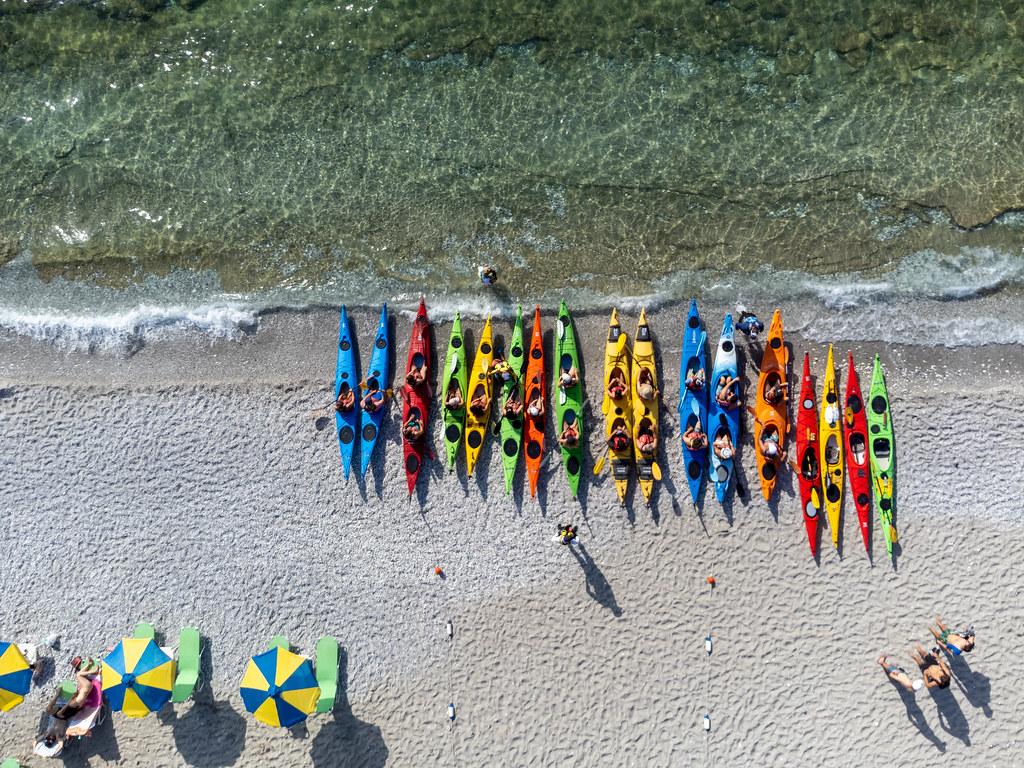 Kajak fahren auf Skopelos, Griechenland: Draufsicht auf viele bunte Kajaks, aufgereiht am Strand von Milia