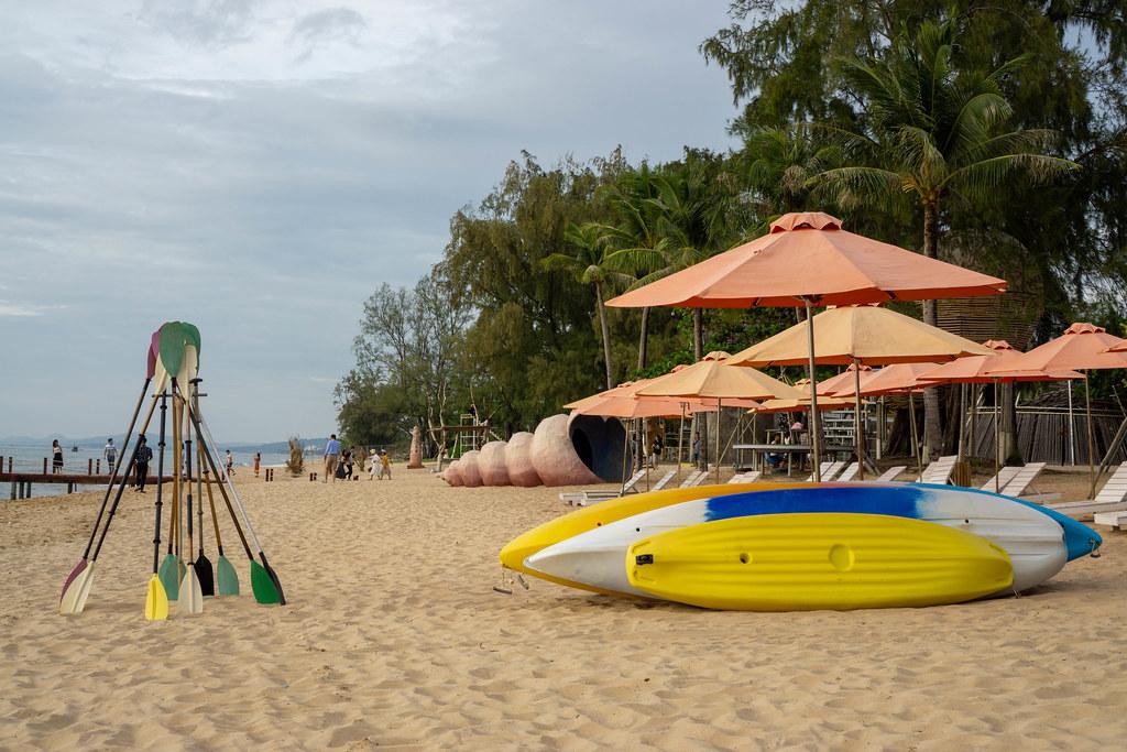 Kajak und Paddel am Strand vom Sunset Sanato Beach Club mit Strandliegen und Sonnenschirmen im Hintergrund