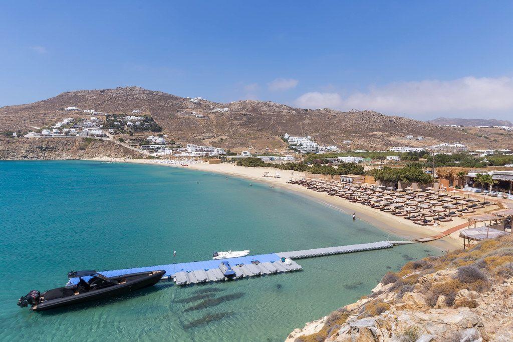 Kalo Livadi Strand auf Mykonos (Griechenland) mit kleiner Seebrücke und schwarzem Motorboot