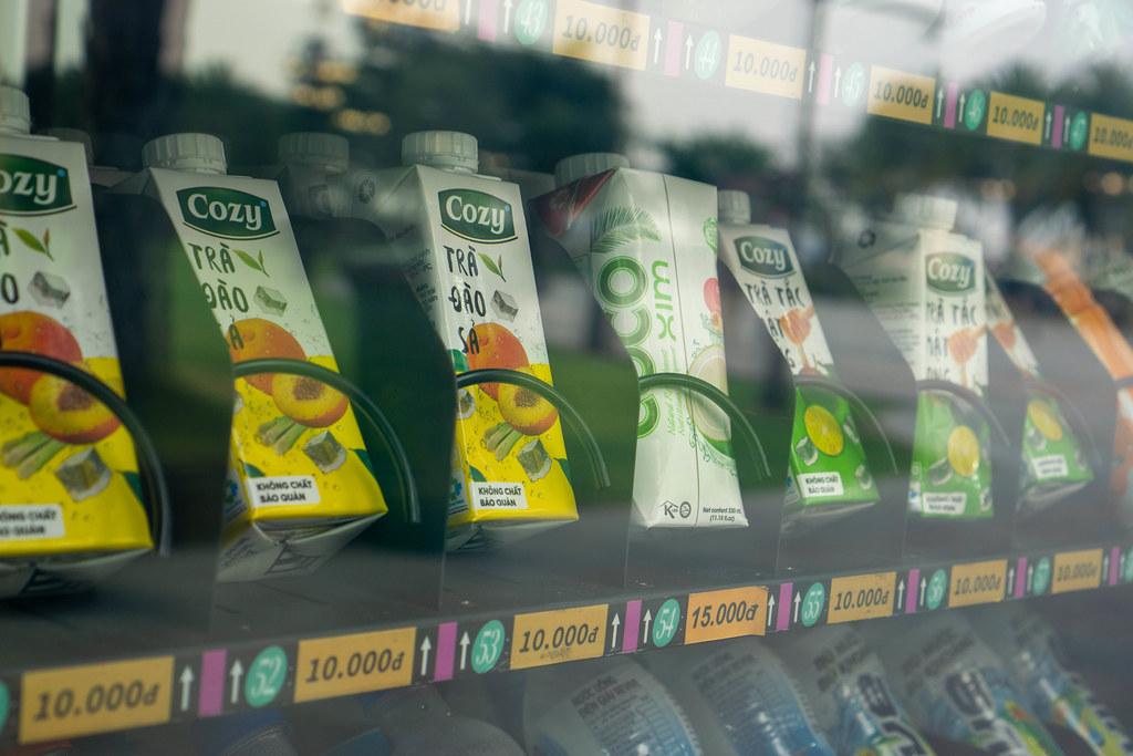 Kalte Getränke in Tetra Paks und Flaschen in einem Getränkeautomaten mit Preisen und Nummern in einem Öffentlichen Park