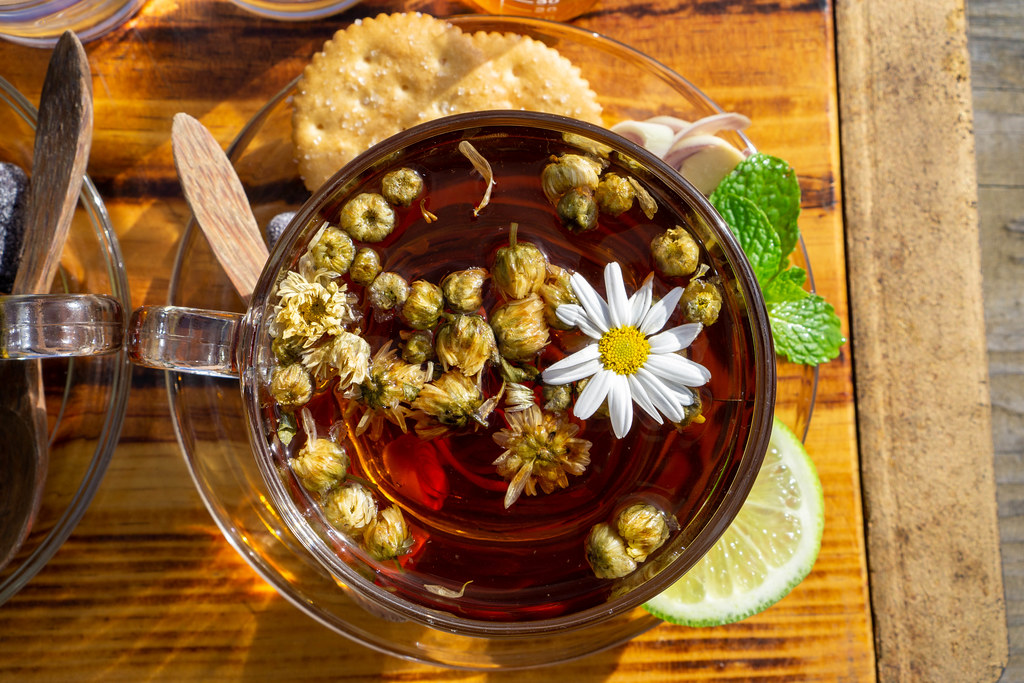 Kamillentee in einer Glastasse auf einem Glasuntersetzer mit Holzlöffel, Keksen, Zitronengras, Minze und Zitrone von oben auf einem Holzbrett fotografiert