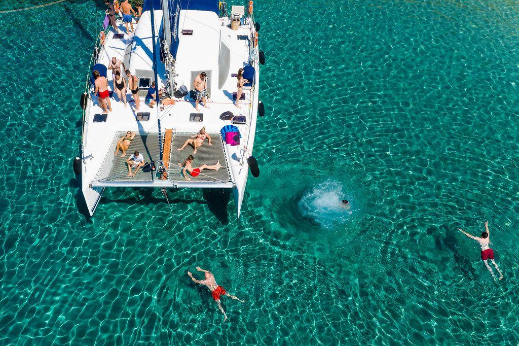 Katamaranfahrt in Milos, Griechenland: Touristen springen vom Boot ins Meer. Entspannung im Urlaub
