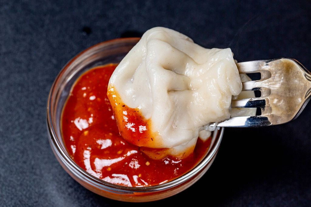 Khinkali soaks in red sauce on a black background