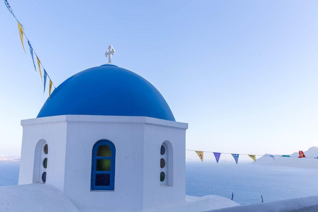 Kirche mit blauer Kuppel und Fahnen auf Santorin mit dem Meer und blauem Himmel