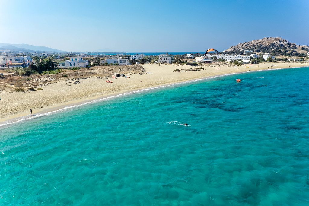 Kite surfing in the blue waters of Naxos at Mikri Vigla beach. Aerial view with headland and village