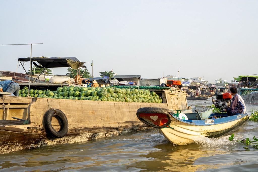Kleine Schiffe und Boote verkaufen verschiedene Früchte wie Wassermelonen und andere Waren auf dem Cai Rang Schwimmenden Markt in Can Tho, Vietnam