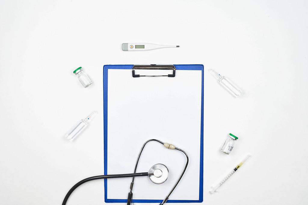 Klemmbrett und Medizinbedarf vor weißem Hintergrund mit Platz für Text