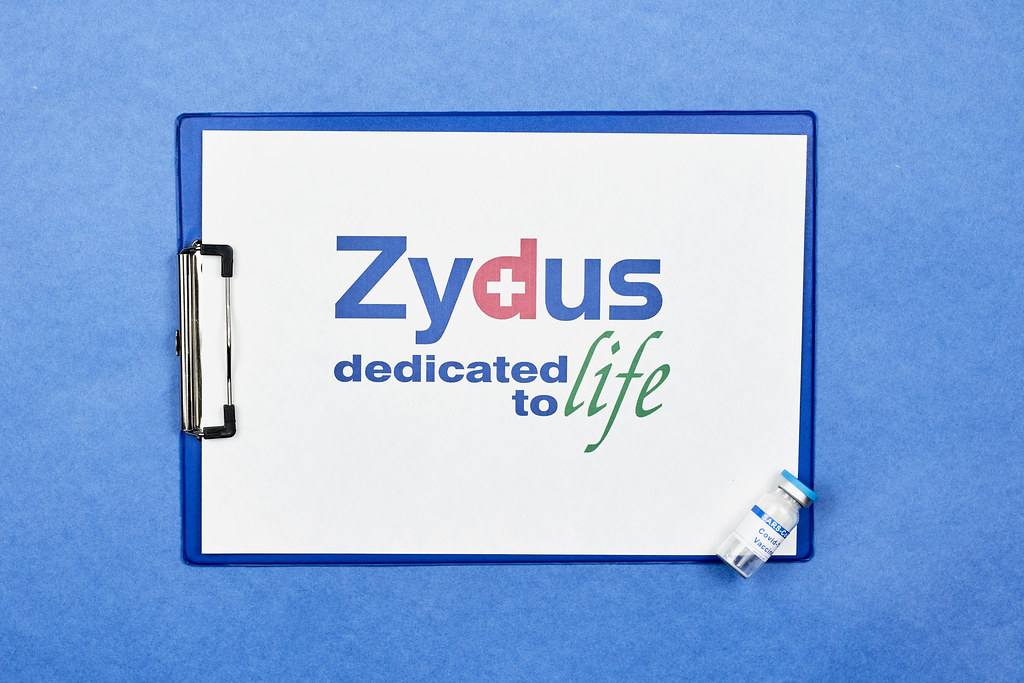 Klemmbrett vor blauem Hintergrund mit Zydus Pharmaceuticals Logo und Corona-Impfstoff Ampulle