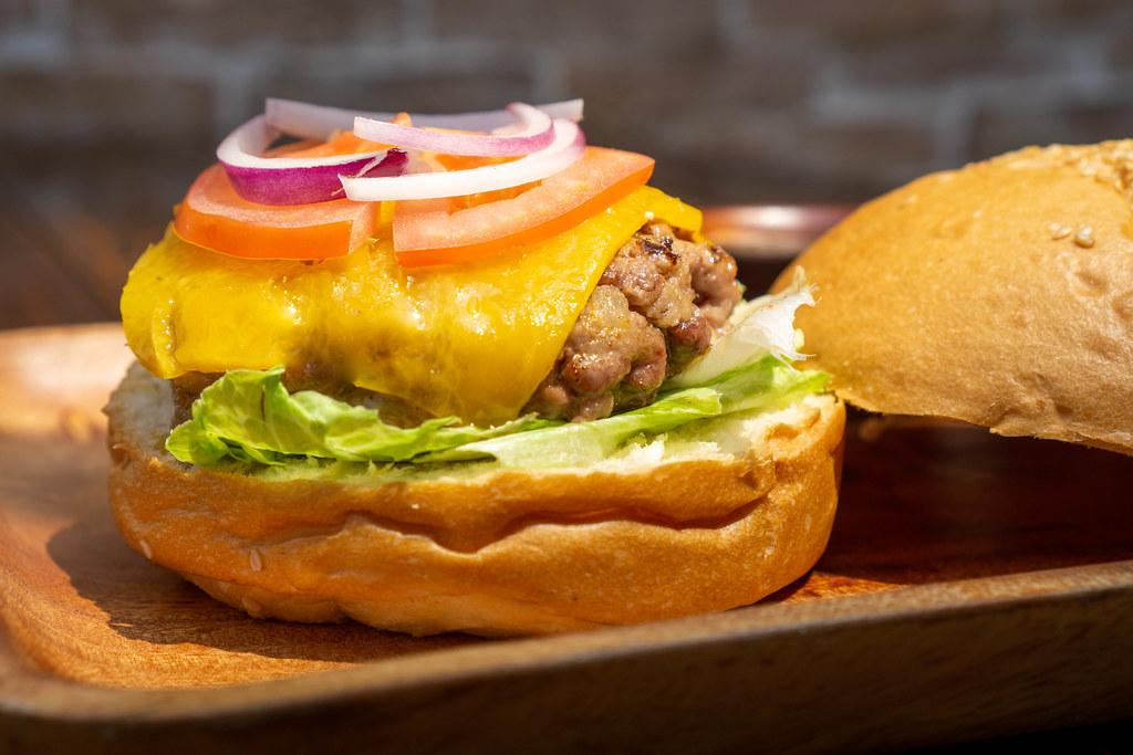 Köfte Burger mit Lammfleisch Patty, Geschmolzenem Käse, Salat, Tomate und Zwiebeln auf einem Holzteller Nahaufnahme