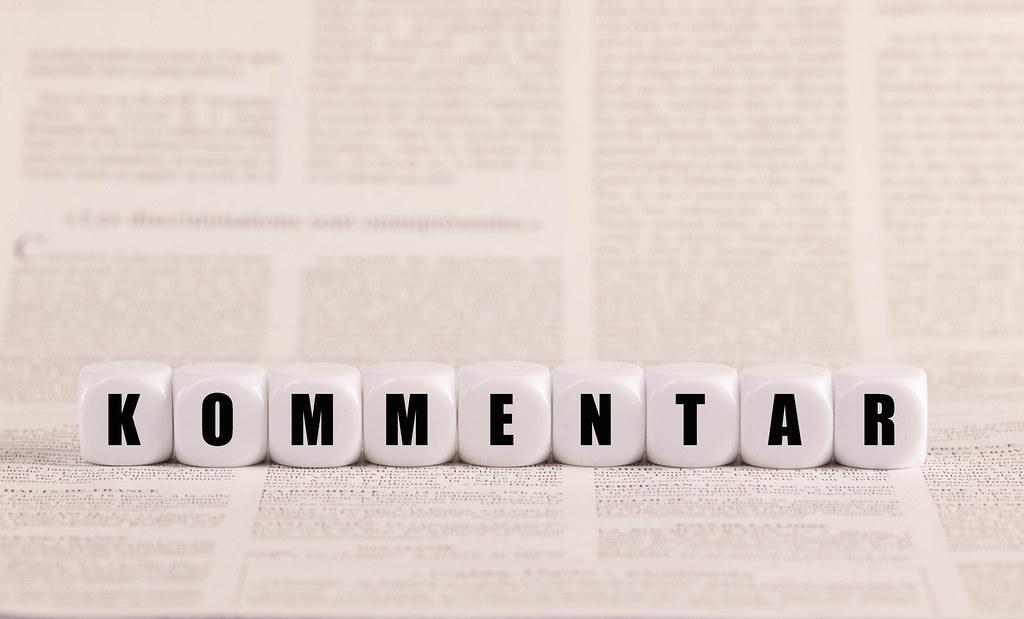 Kommentar, Würfel, Holzwürfel auf Zeitungspapier