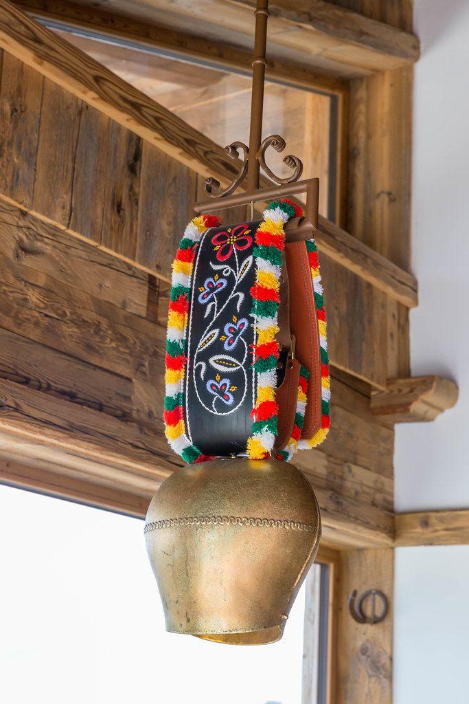 Kuhglocke mit buntem Band hängt in einem Gebäude aus Holz in den Alpen in Tirol
