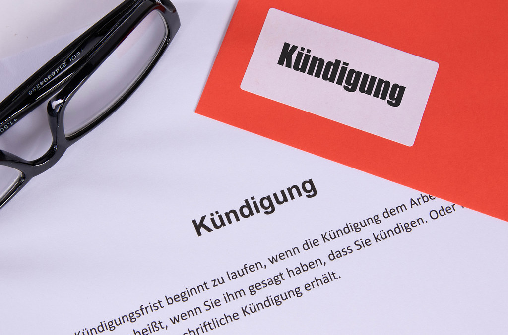 Kündigung document with glasses and red envelope