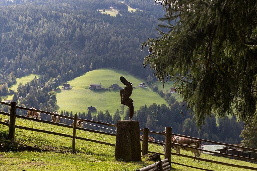 Kunst und Landschaft in den Alpen: eine Skulptur und Kühen auf der Weide im Hintergrund in Alpbach