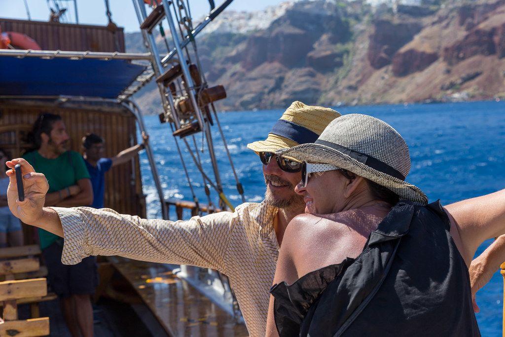 Lächelndes Touristenpaar macht Urlaubs-Selfie auf dem Segelboot vor der Küste Santorinis