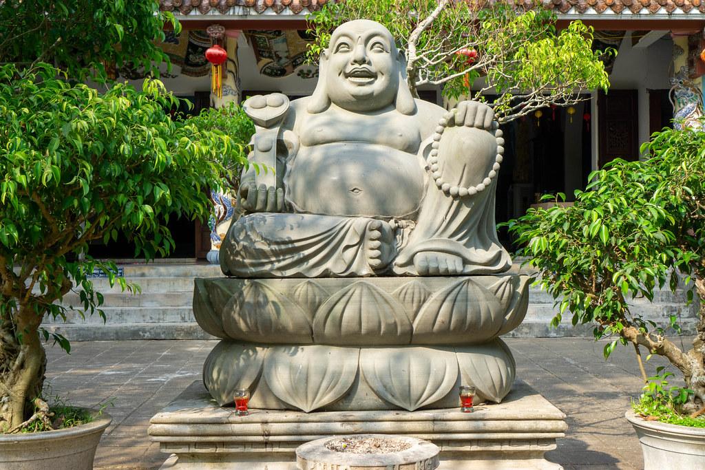 Lachender Buddha Statue mit kleinen Bäumen in Blumentöpfen vor der Tam Thai Pagode bei den Marble Mountains in Da Nang, Vietnam