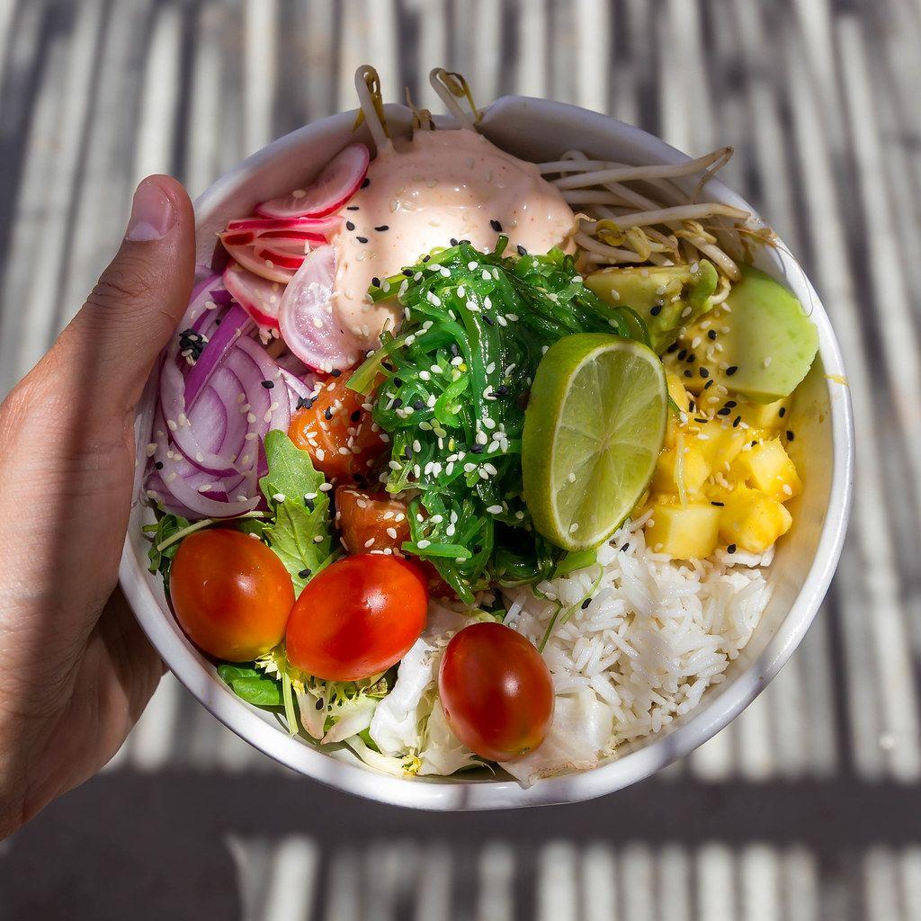 Lachs-Poke-Bowl mit Reis, Limette, Kirschtomaten, Radieschen, Sprossen, Avocado, Kräutern. Draufsicht