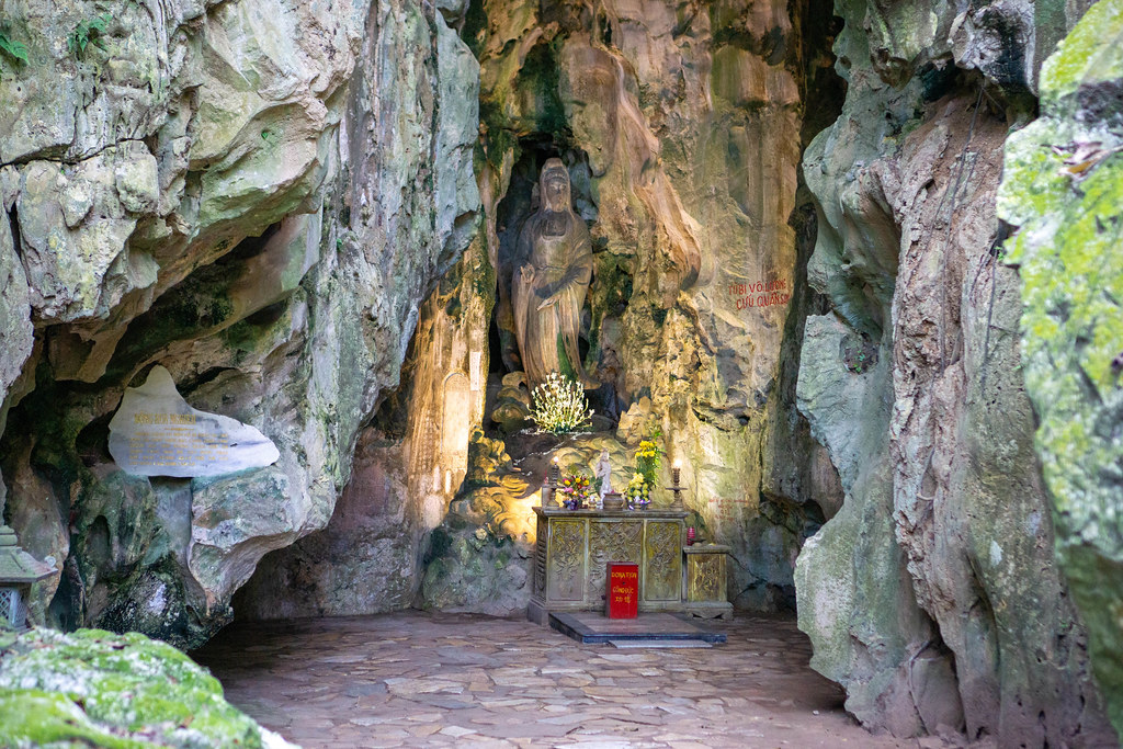 Lady Buddha Statue carved in a Stone Wall inside a Cave with Offerings and Donation Box in front at Marble Mountains, Vietnam