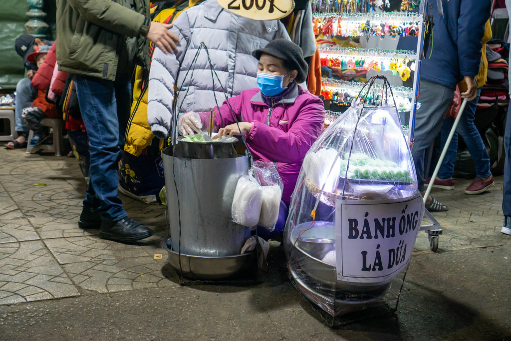 Lady selling Vietnamese Pineapple Leaf Tube Cake Banh Ong La Dua at the famous Night Market in Da Lat, Vietnam