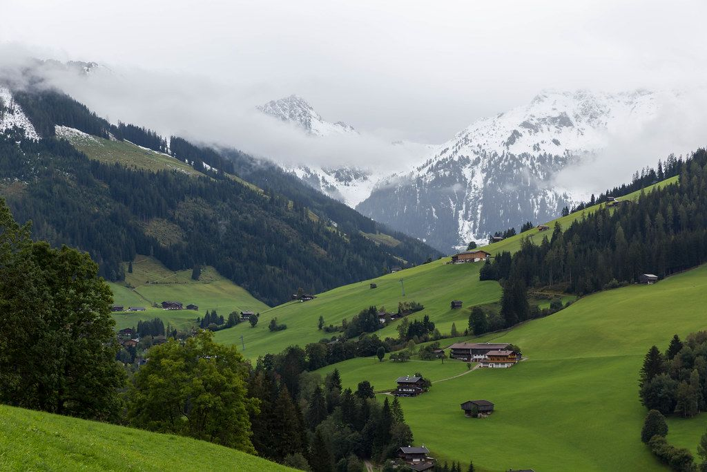 Landscape of the Alpbach valley with typical Tyrolean wooden houses and snowy mountains in the background