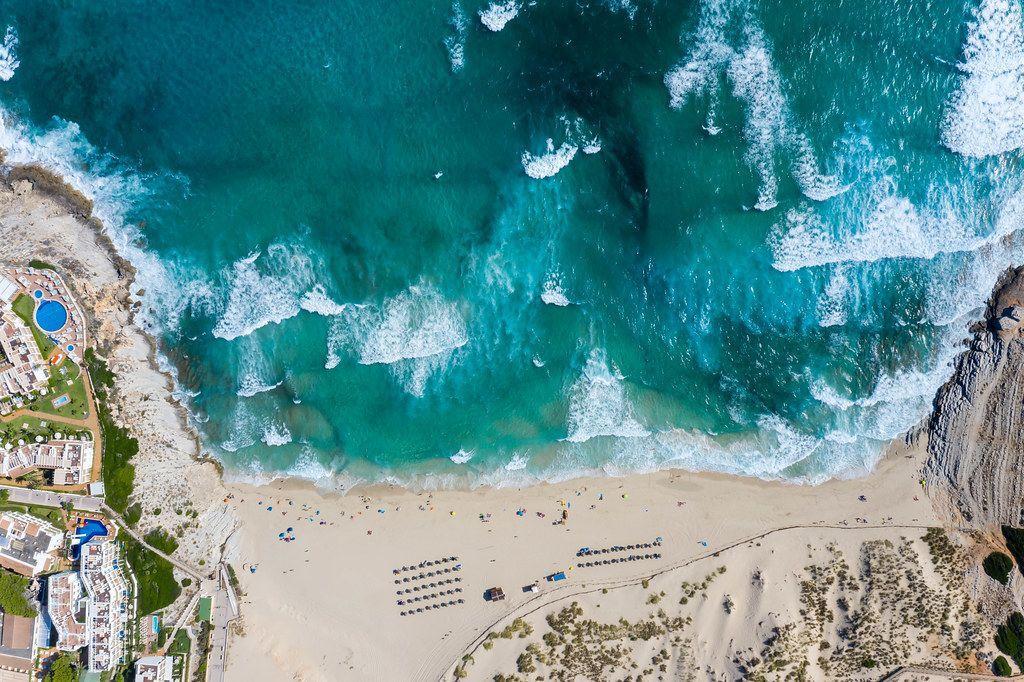 Langer Sandstrand mit Dünen und Wellen. Drohnenaufnahme von Cala Mesquida auf Mallorca