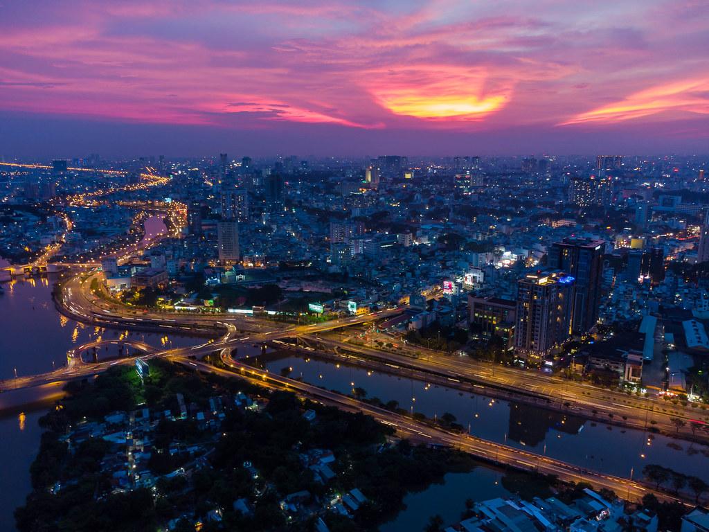 Langzeitbelichtung aus der Luft mit einer Drohne von einer Brücke über dem Saigon Fluss bei Sonnenuntergang in Ho Chi Minh Stadt, Vietnam