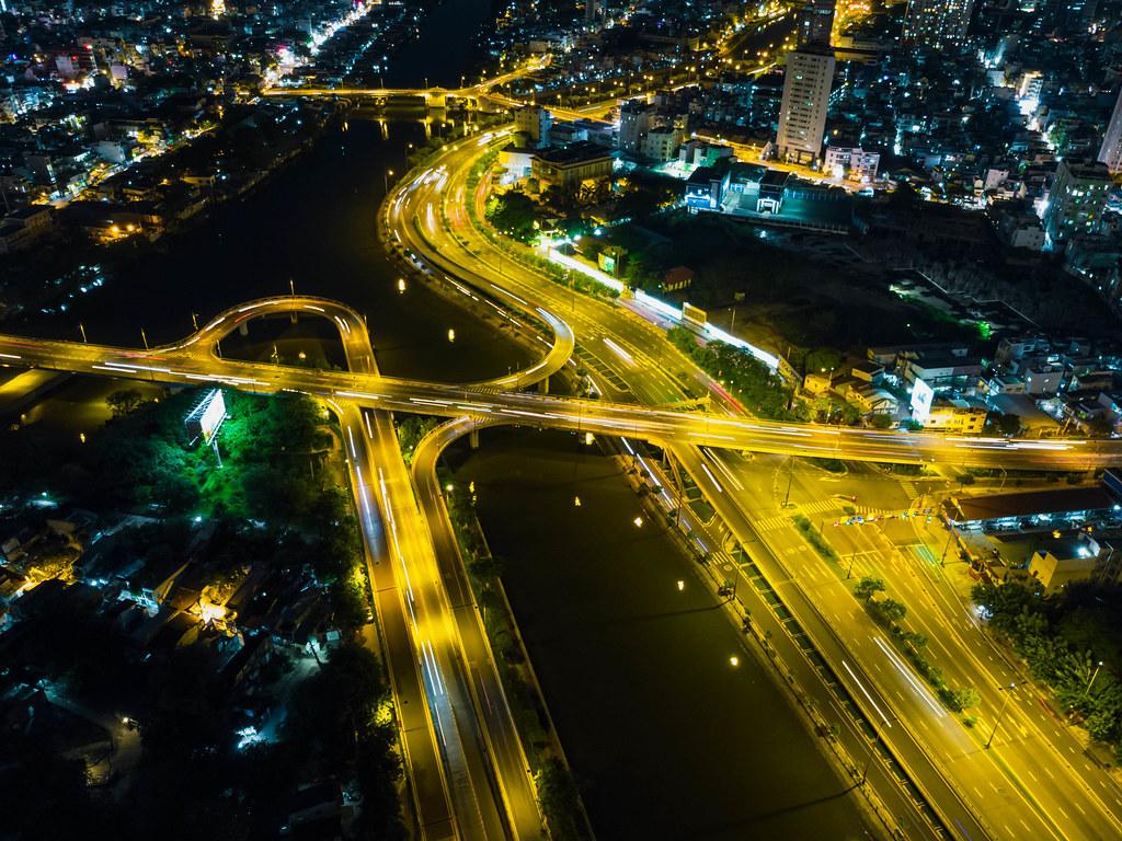 Langzeitbelichtung von einer Brücke welche 3 Stadtbezirke verbindet aus der Luft mit einer Drohne bei Nacht in Ho Chi Minh Stadt, Vietnam