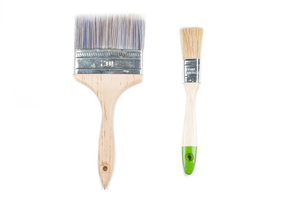 Large and small wooden paint brushes on a white background