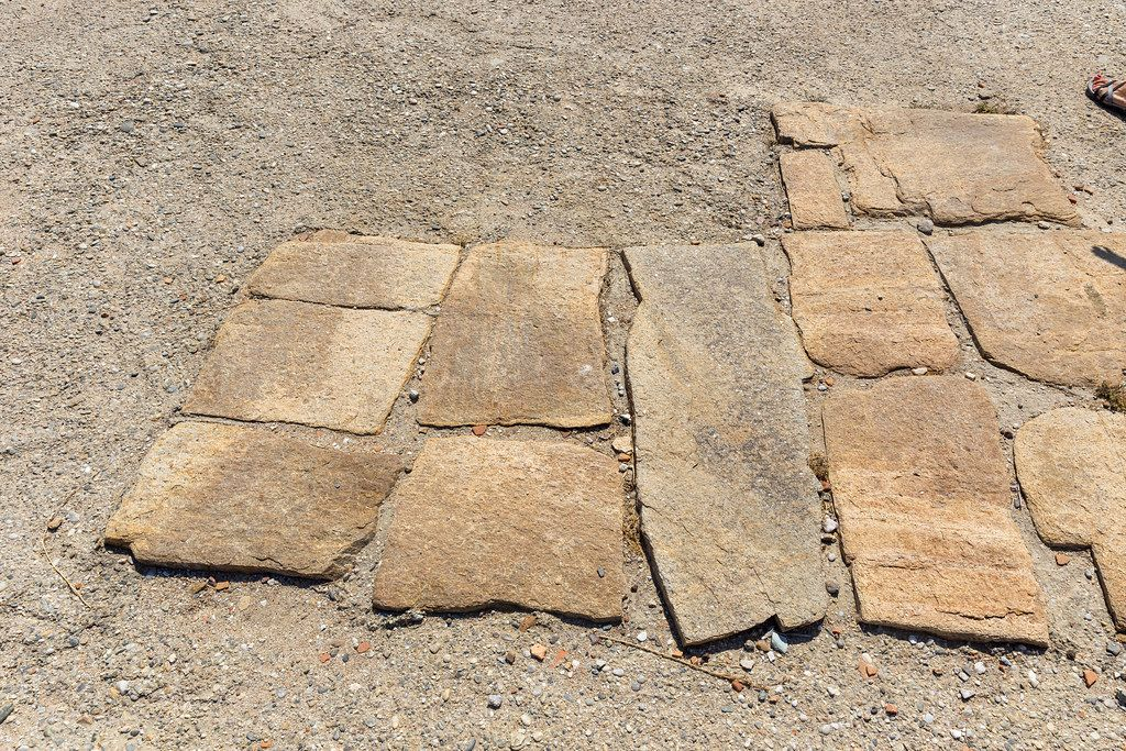 Large flat stones of gneiss: the paved ground of the Agora of the Competaliasts, ancient market on Delos