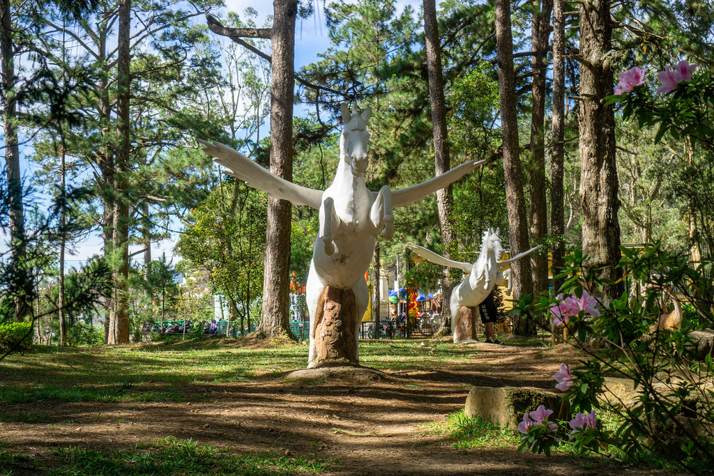 Large Pegasus Statues in a Park with Tall Trees, Plants and Flowers at the Bao Dai King Palace in Da Lat, Vietnam