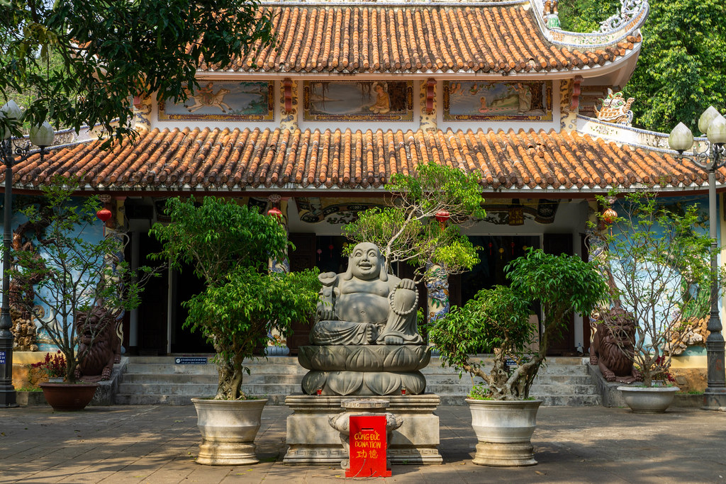 Laughing Buddha Statue with Donation Boxand Trees in Plant Pots in front of Tam Thai Pagoda at Marble Mountains in Da Nang, Vietnam