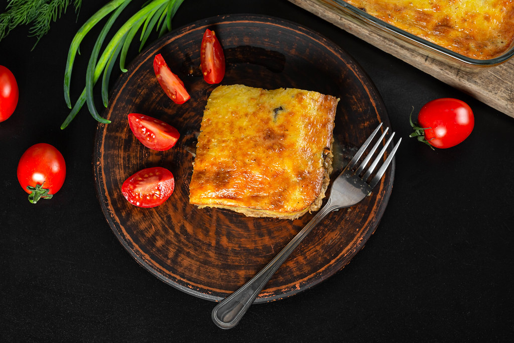 Layered casserole with meat, cheese and mushrooms on a plate with fresh tomato slices