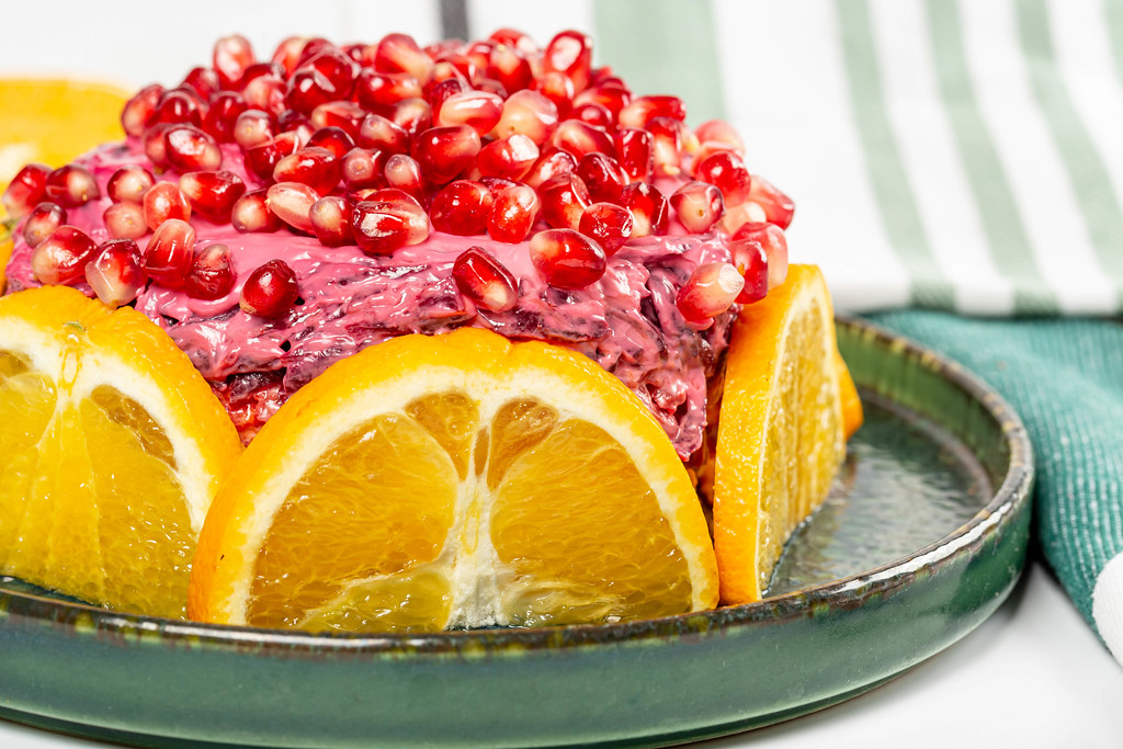 Layered salad composed of pickled herring covered with layers of boiled grated vegetables, orange and pomegranate
