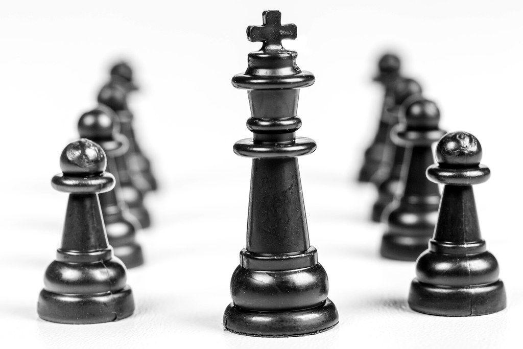 Leader and teamwork concept for success. Black wooden chess