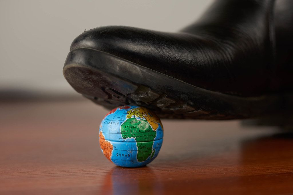 Leather shoes tramples Earth. Post coronavirus world or ecological and environmental problems concepts