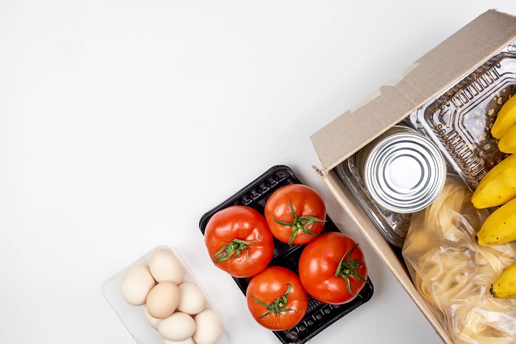 Lebensmittel spenden: Karton mit Keksen, Nudeln, Tomaten, Bananen, Eiern, Blechdosen und Platz für Text