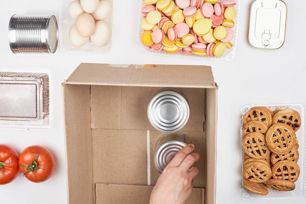 Lebensmittel wie Tomaten, Eier und Süßigkeiten spenden, Blechdosen in einen Karton stellen