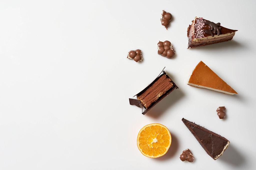 Leckere Torten: Schokoladentorte, Käsekuchen, Tiramisu vor weißem Hintergrund mit Platz für Text