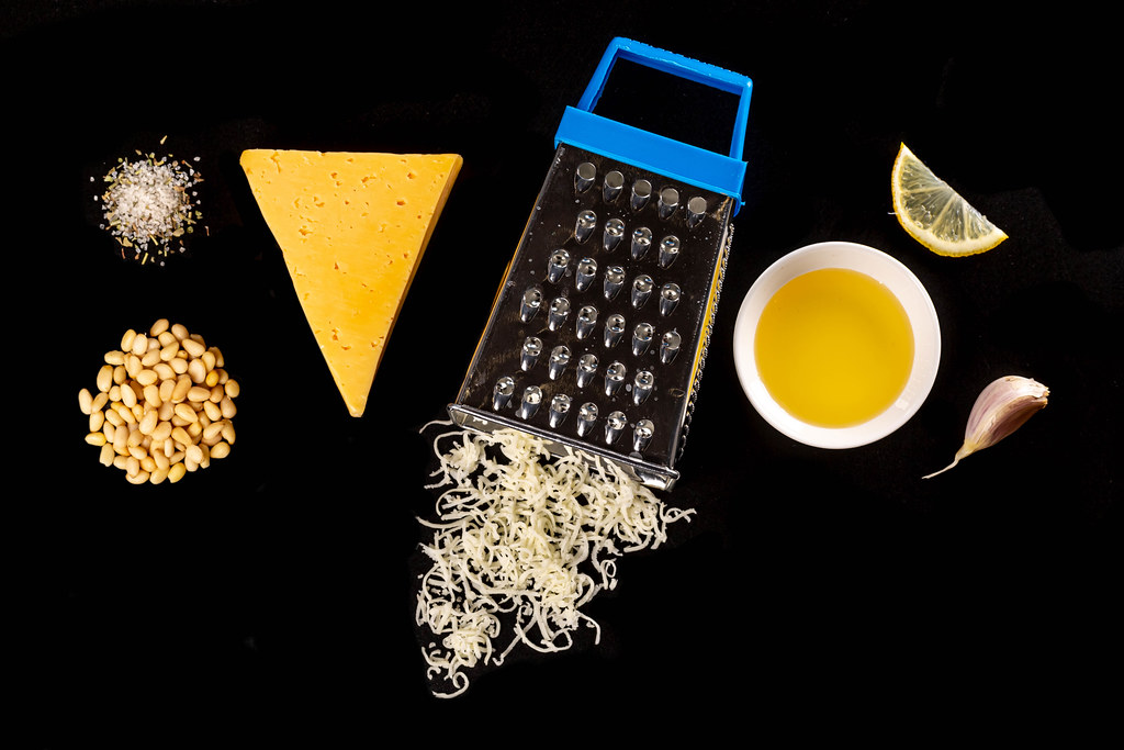 Lemon, cheese, pine nuts, olive oil and grater, top view