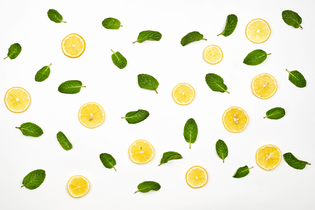Lemon slices and green leaves on white background