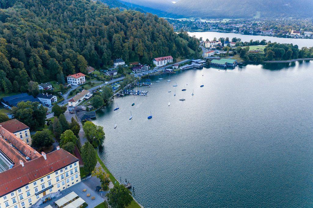 Liegeplatz für Segelboote mit zwei kleinen Seebrücken am Tegernsee. Luftaufnahme im Herbst