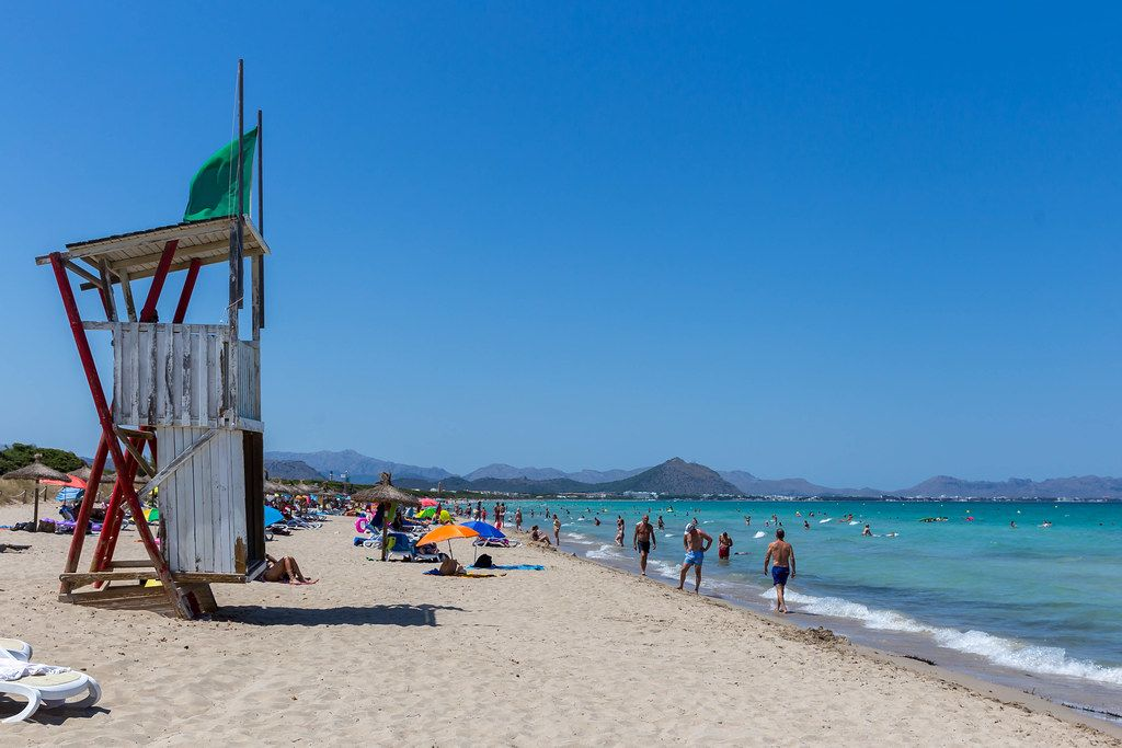 Lifeguard tower on the beach of Can Picafort in Mallorca with many tourists in summer 2020