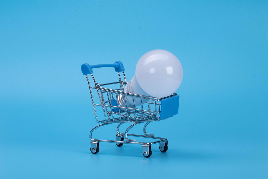 Light bulb in shopping cart on blue background