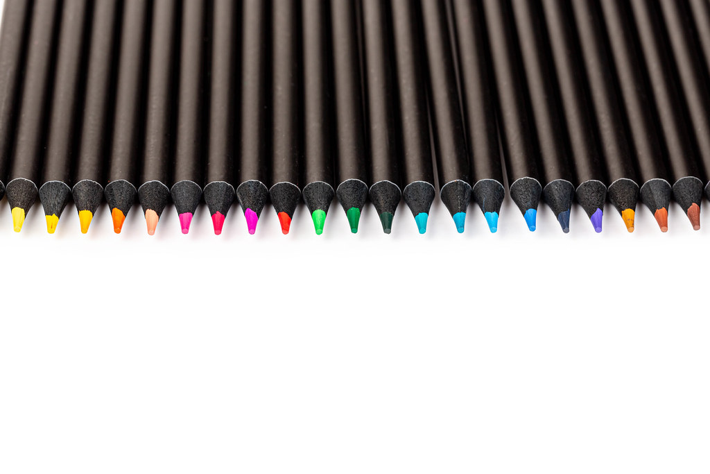 Line of colored pencils on white